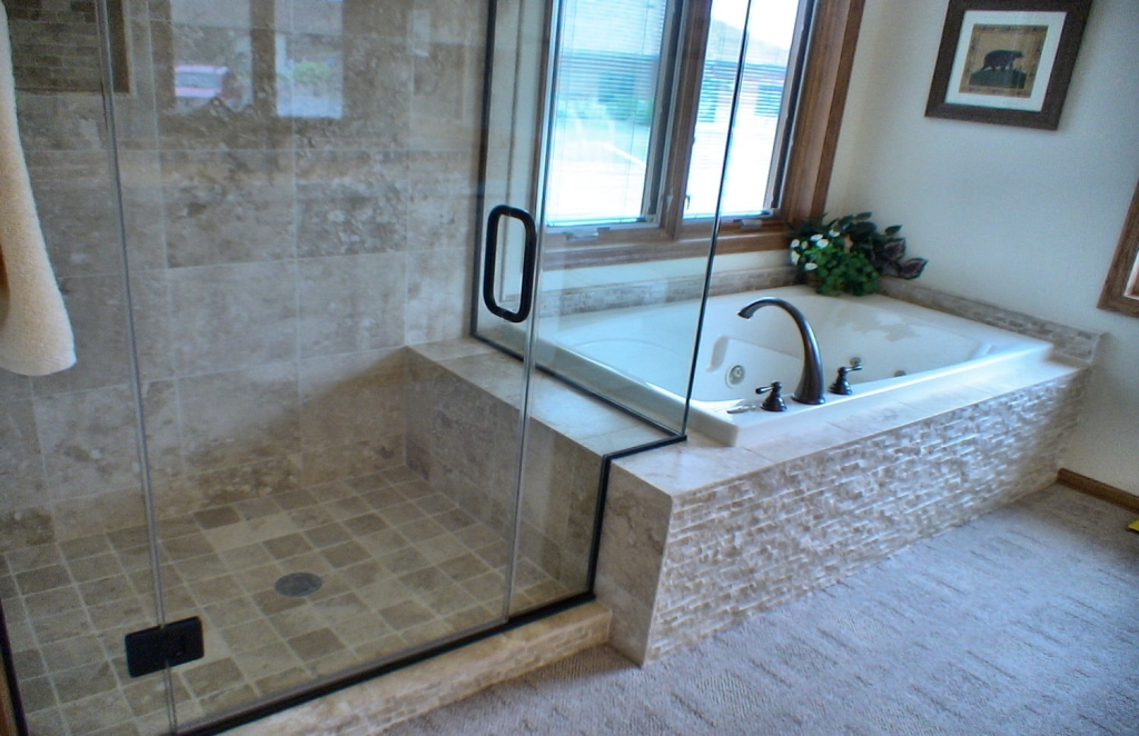 glass shower enclosure with tile tub
